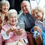 four-happy-seniors-looking-at-smartphone